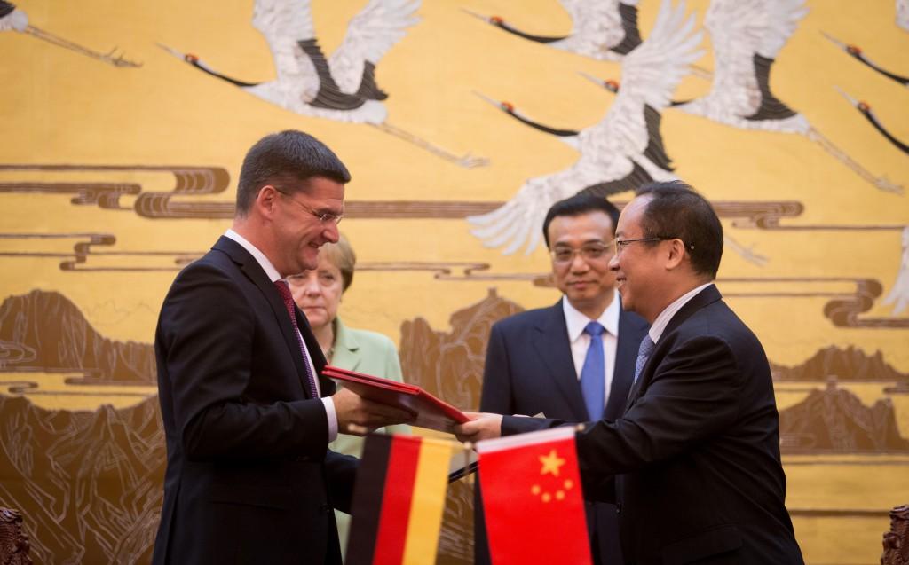 Oliver Frese, Mitglied des Vorstands der Deutschen Messe AG (vorne links), und Dr. Gong Xiaofeng, Executive Vice Chairman vom CCPITECC (vorne rechts) unterzeichneten in Gegenwart von Bundeskanzlerin Angela Merkel (hinten links) und dem chinesischen Premierminister Li Keqiang (hinten rechts) in Beijing den Partnerschaftsvertrag für die IT-Leitmesse CeBIT (Foto: Deutsche Messe / picture alliance / dpa / Nietfeld)