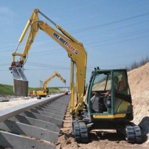 Der acht Tonnen schwere Minibagger von HKL füllt die Zwischenräume der Stützmauer mit einem Gemisch aus Erde, Schotter und Mineralien (Foto: HKL)