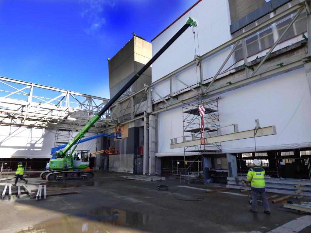 Einsatz auf dem Hallendach: der SENNEBOGEN 613 hebt Stahlträger für die neue Dachkonstruktion ein